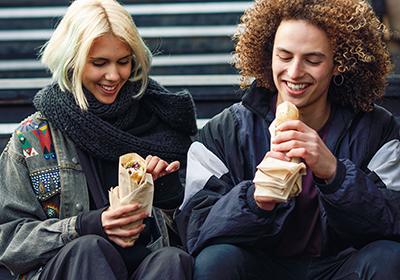 giovani metropolitani mangiano cibo etnico